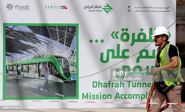 A worker walks past a giant poster on May 4 2016 at a construction site of a section of the Saudi capital Riyadh's $225 billion metro system The...