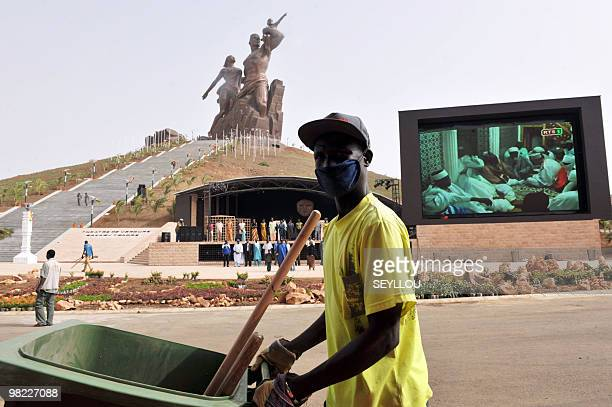 A worker walks past a giant screen in front of the 'African Renaissance Monument' on April 2 2010 in Dakar in preparation for the April 3...
