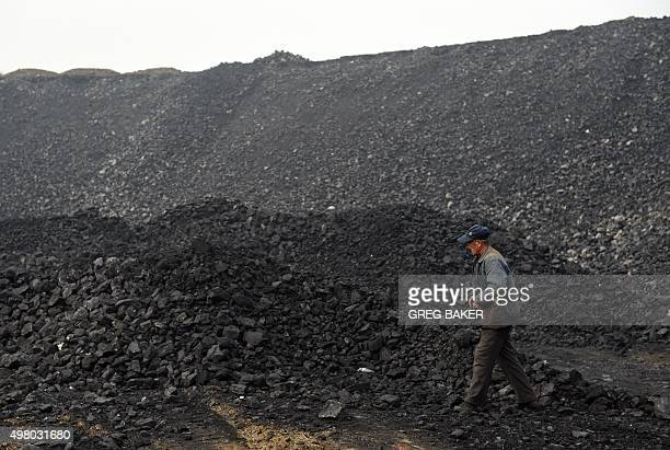 A worker walks past a pile of coal near a coal mine in Datong in China's northern Shanxi province on November 20 2015 China will not improve on its...