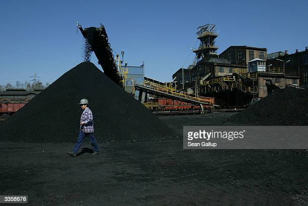 A worker walks past a pile of freshlymined high quality coal at the Wieczorek coal mine April 14 2004 in Katowice Poland Poland will be the largest...