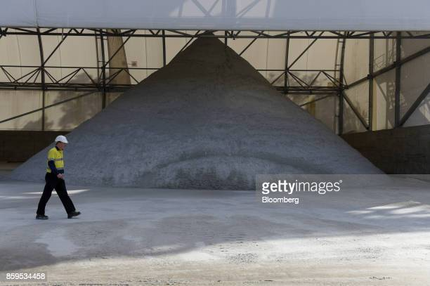 A worker walks past a pile of lithium ore at a Talison Lithium Ltd site a joint venture between Tianqi Lithium Corp and Albemarle Corp in Greenbushes...