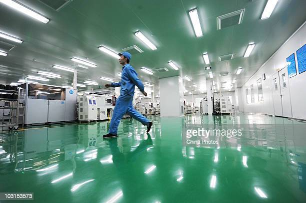 Worker walks past a production line at the Yingshan Digital Technology Culture Development Company on July 29, 2010 in Shifang of Sichuan Province,...