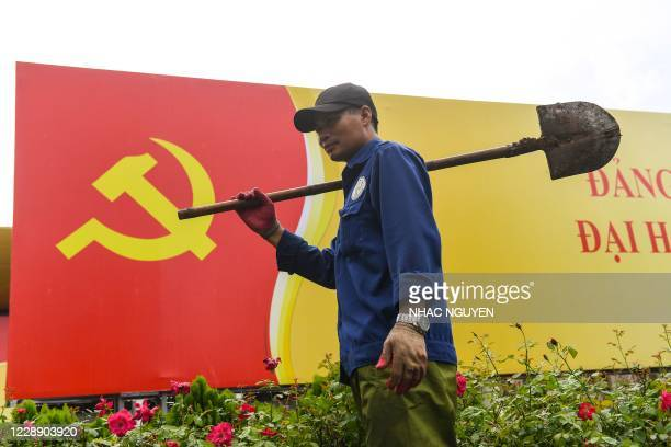 Worker walks past a signboard with the Communist Party flag in Hanoi on October 5 as the city prepares for the upcoming party congress.