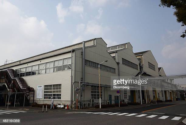 A worker walks past a Toyota Motor Corp plant in Toyota City Aichi Prefecture Japan on Tuesday Feb 25 2014 Inside Toyota Motor Corps oldest plant...