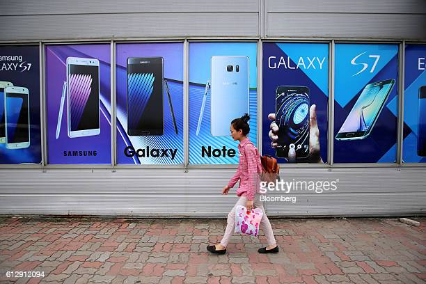 A worker walks past an advertisement for the Samsung Electronics Co Galaxy S7 smartphone near the Samsung Electronics Vietnam Co Plant at Yen Phong...