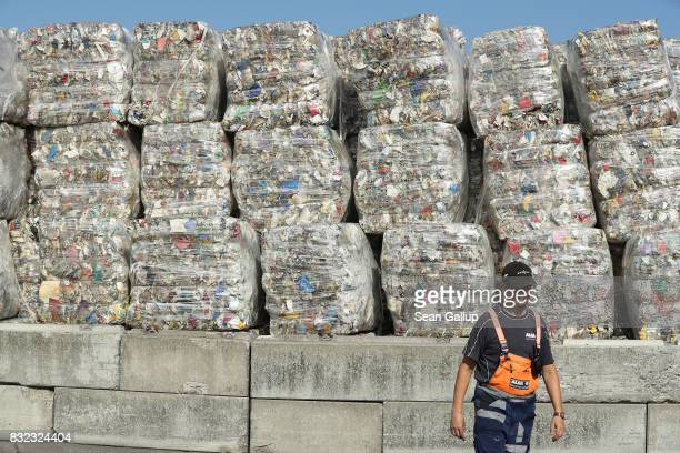 A worker walks past bales of sorted trash at the ALBA sorting center for the recycling of packaging materials on August 15 2017 in Berlin Germany The...
