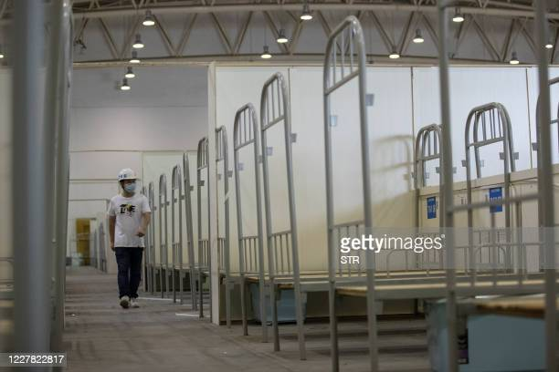 Worker walks past bed frames as workers demolish installations at Wuhan's largest makeshift hospital built to treat patients infected by the COVID-19...