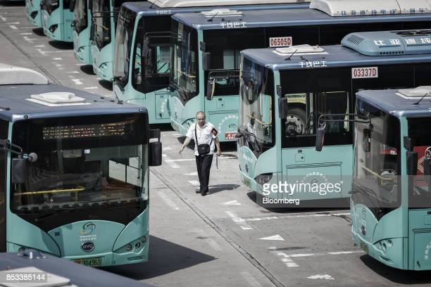A worker walks past BYD Co electric buses parked at a public transportation hub in Shenzhen China on Wednesday Sept 20 2017 China the worlds biggest...