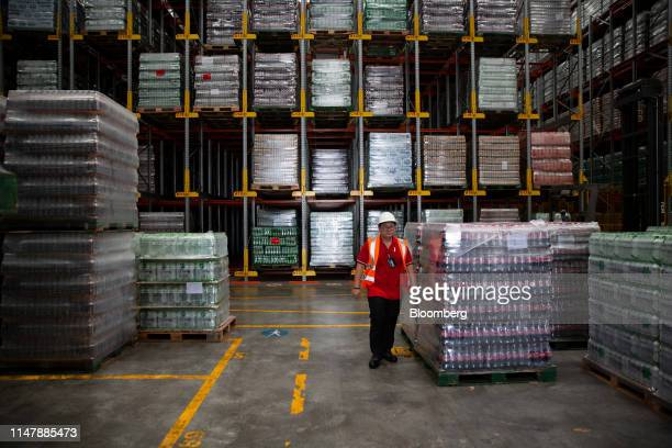 A worker walks past CocaCola Co brand drinks inside a warehouse at the CocaCola Cambodia Bottling Plant operated by Cambodia Beverage Co which is a...