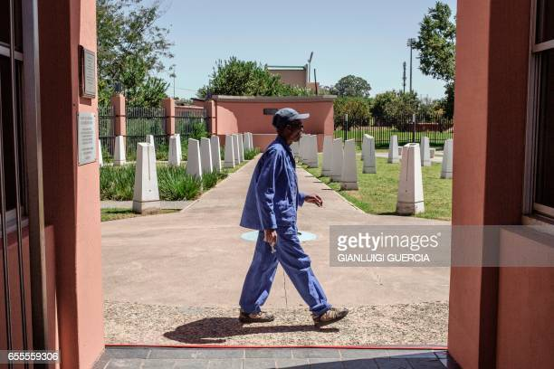 A worker walks past commemorative stones with inscribed with victim's names at the Sharpeville Heritage Memorial compound on the eve of the 57th...