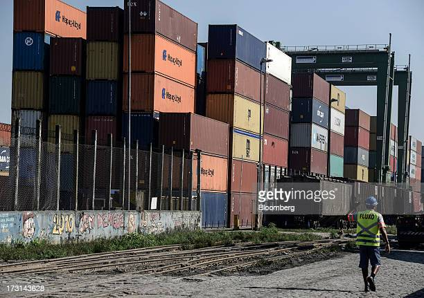 A worker walks past containers waiting to be loaded at the Port of Santos in Santos Brazil on Friday July 5 2013 Rising borrowing costs and the...