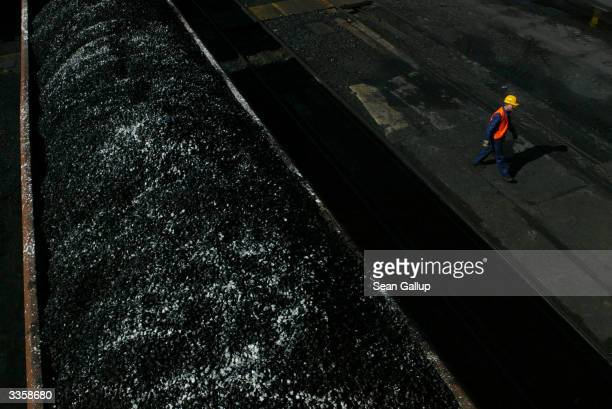 A worker walks past freshlymined high quality coal awaiting transport on a train at the Wieczorek coal mine April 14 2004 in Katowice Poland Poland...