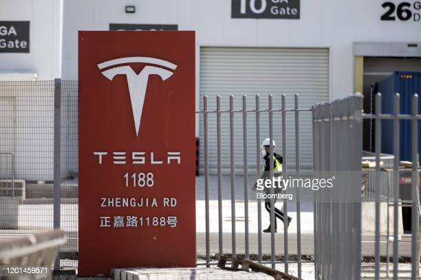A worker walks past gates at the Tesla Inc Gigafactory in Shanghai China on Monday Feb 17 2020 Tesla has fully resumed deliveries of its Chinabuilt...
