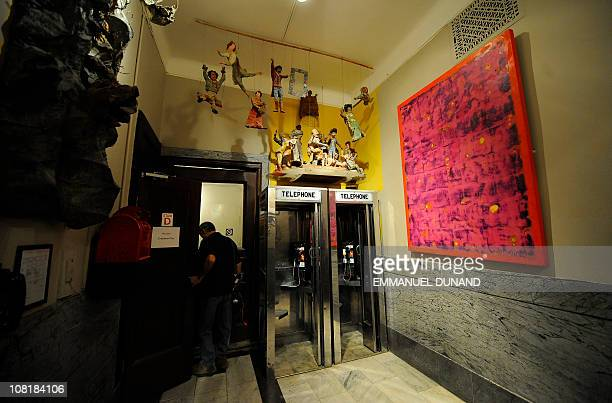 A worker walks past phone booth set up in the lobby at the Chelsea Hotel in New York January 10 2011 The Chelsea Hotel a haven for struggling artists...