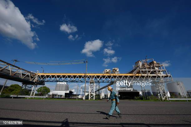A worker walks past pipelines in Nagoya Japan on Tuesday July 31 2018 Japan is scheduled to release trade balance figures for July on Aug 16...