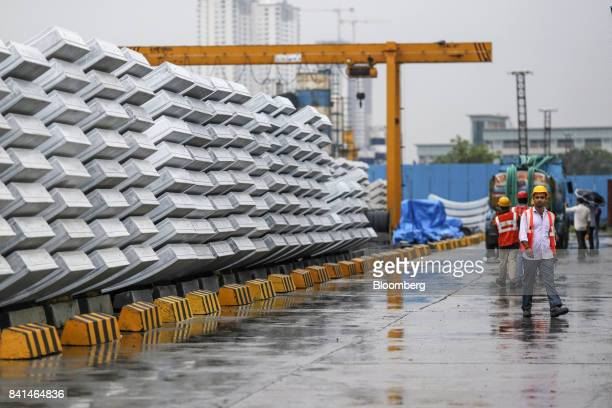 A worker walks past precast concrete tunnel segments sitting stacked outside at the Mumbai Metro Rail Corp casting yard in Mumbai India on Monday Aug...