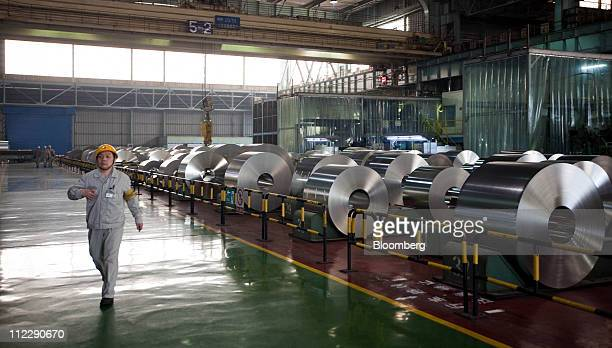 A worker walks past rolls of steel at the Baosteel Group Corp facilities in Shanghai China on Friday April 15 2011 Baosteel Group is the supplier of...