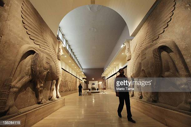 A worker walks past sculptures of humanheaded bulls in the renovated Assyrian room at Iraq's National Museum on December 8 2011 in Baghdad Iraq The...