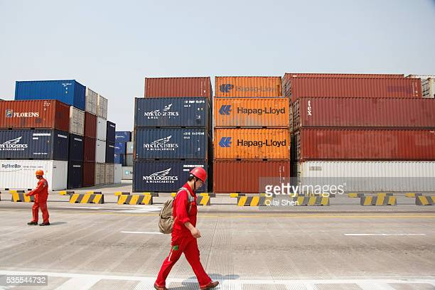 Worker walks past stacked containers at the Yangshan Deepwater Container Port in Shanghai, China on 02 June 2011. Shanghai is now the world's busiest...