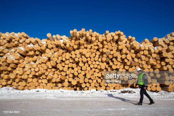 Worker walks past stacks of logs in the yard at the Sokol Timber Company JSC woodworking plant, operated by Segezha Group, in Sokol, Russia, on...