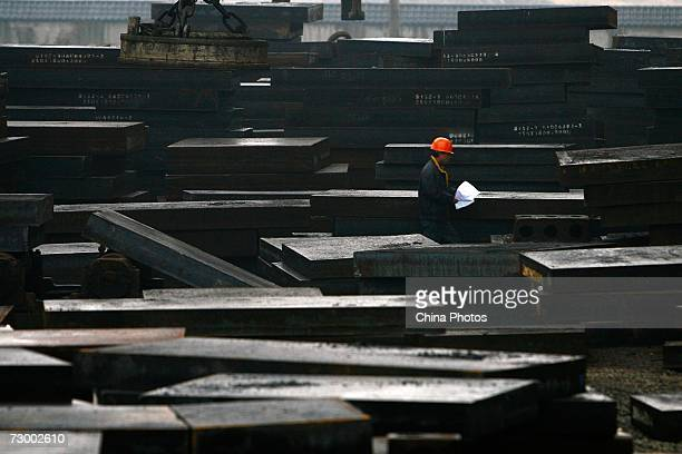 A worker walks past steel ingots at a Shanghai Baosteel Group factory January 15 2007 in Shanghai China According to state media Baosteel is...