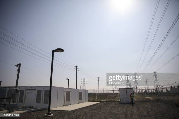 A worker walks past Tesla Inc Powerpacks and inverters at the Southern California Edison Co Mira Loma energy storage system facility in Ontario...