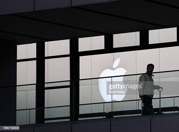 A worker walks past the Apple Inc logo in the Sanlitun area of Beijing China on Friday Nov 9 2012 China's retail sales exceeded forecasts and...