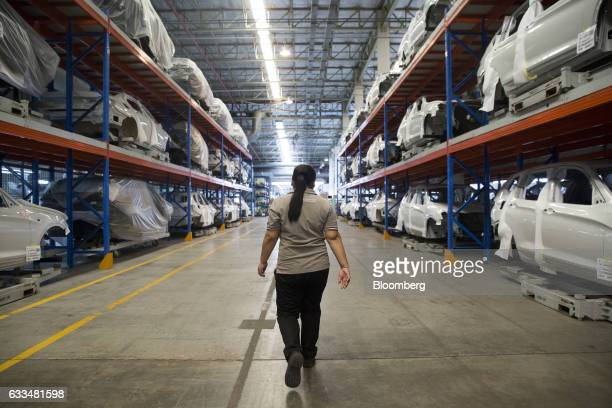 A worker walks past the bodies of BMWX5 xDrive40e M Sport plugin hybrid vehicles stacked in a warehouse at the BMW AG assembly plant in Amata Rayong...