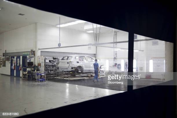 A worker walks past the body of a BMWX5 xDrive40e M Sport plugin hybrid vehicle inside a quality control room at the BMW AG assembly plant in Amata...