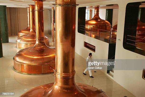 A worker walks past the giant copper vats that contain the brew of heated barley mash known as wort mixed with hops that will become PilsnerUrquell...