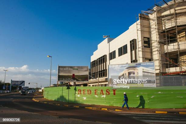 A worker walks past the new underconstruction Capital Bank Botswana Ltd headquarters office in the central business district of Gaborone Botswana on...