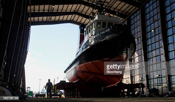 A worker walks past the Pacer tugboat as it undergoes repairs at the Seaspan Vancouver Shipyard in North Vancouver British Columbia Canada on...