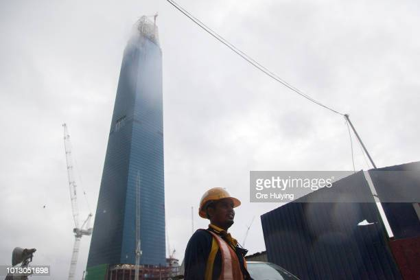 A worker walks past the Tun Razak Exchange Tower at the project site on July 30 2018 in Kuala Lumpur Malaysia The Tun Razak Exchange one of the 1MDB...