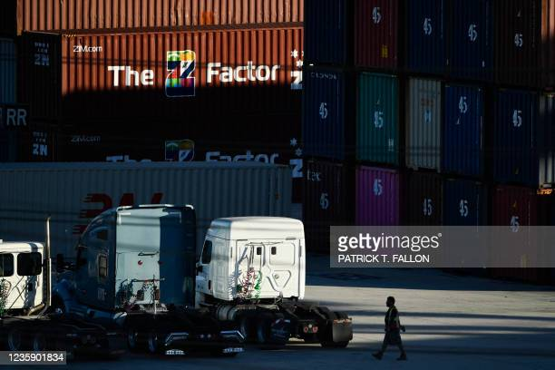 Worker walks past trucks and cargo shipping containers at the Port of Los Angeles on October 15, 2021 in San Pedro, California. - The port, North...