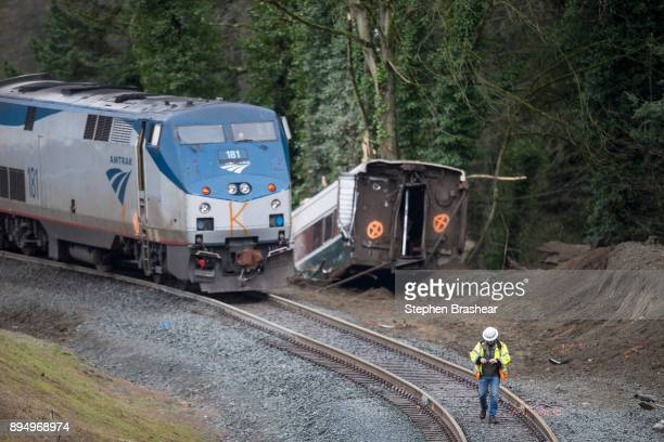 A worker walks the tracks at the scene of a Amtrak train derailment on December 18 2017 in DuPont Washington At least six people were killed when a...