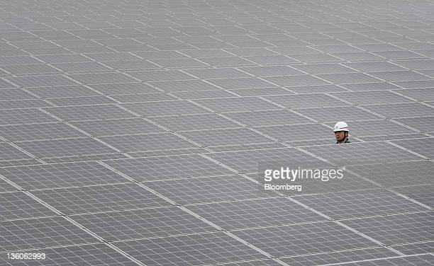 A worker walks through Kyocera Corp solar panels at the Ohgishima solar power plant operated by Tokyo Electric Power Co in Kawasaki City Kanagawa...