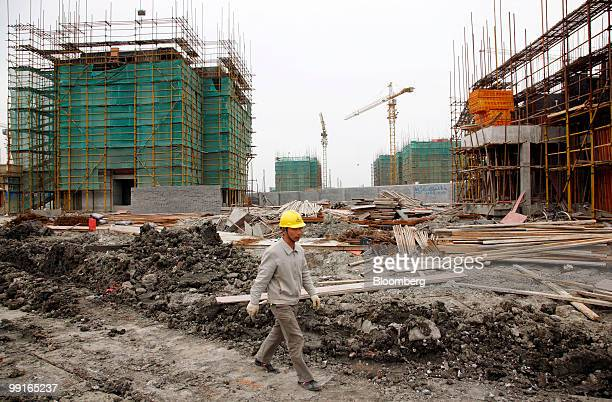 A worker walks through the construction site for a residential development in Shanghai China on Thursday May 13 2010 Shanghai's municipal government...