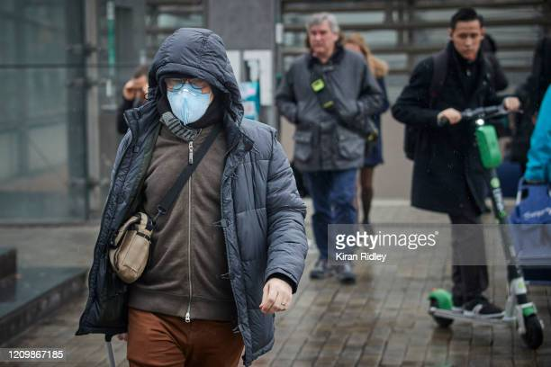 A worker walks to work wearing a face mask as two new cases of Coronavirus were announced in the French capital on March 2 2020 in Paris France...