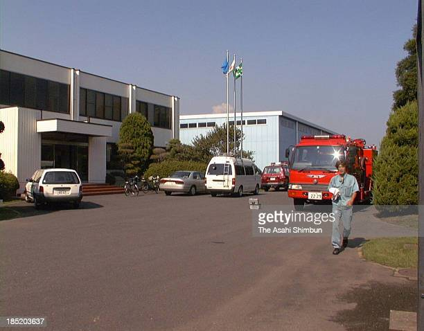 A worker walks toward the main gate while fire fighting vehicle is on standby at nuclear fuel cycle company JCO is seen on September 30 1999 in Tokai...