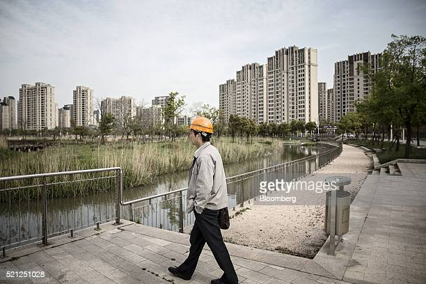 A worker walks towards a pond as residential buildings stand in the distance in the Jiading district of Shanghai China on Monday April 11 2016...