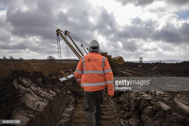 A worker walks towards a sideboom tractor operated by SpiecapagAktor JV as it lays welded pipe sections into a trench at the 685km point during the...