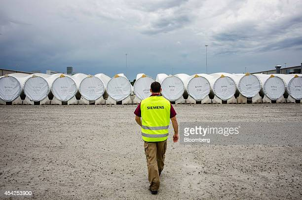 A worker walks towards finished turbine blades awaiting transport at the Siemens AG turbine blade plant in Fort Madison Iowa US on Wednesday Aug 20...