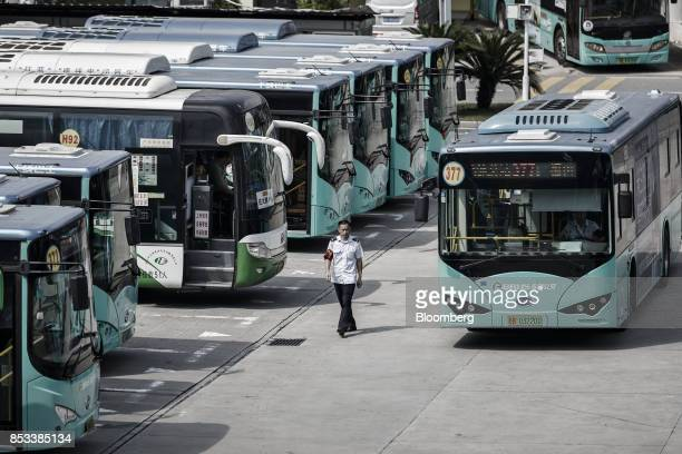 A worker walks while a BYD Co electric bus arrives at a public transportation hub in Shenzhen China on Wednesday Sept 20 2017 China the worlds...