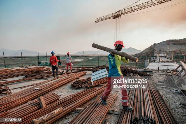 A worker walks with a piece of wood on his shoulder at the Grand Ethiopian Renaissance Dam near Guba in Ethiopia on December 26 2019 The Grand...