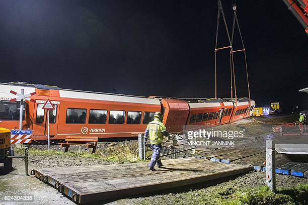 A worker walks work near a derailed passenger train prepared to be removed after a crash with a milk tanker near Winsum on November 18 2016 Several...