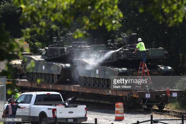 A worker washes one of two M1A1 Abrams tanks that are loaded on rail cars at a rail yard on July 2 2019 in Washington DC President Trump asked the...