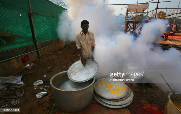 A worker washes the utensils as fumigation takes place during the sanitization of Shivaji Park area a day after lakhs of followers gathered on Dr...