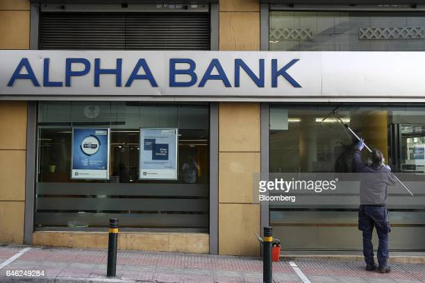 A worker washes the windows of an Alpha Bank AE bank branch in Athens Greece on Tuesday Feb 28 2017 Greeces auditors are pulling together a list of...
