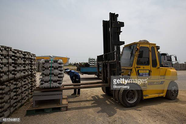 A worker watches a Hyundai Heavy Industries Co HDF 707 forklift truck driver weigh a stack of aluminum ingots from a truck at the Public Procurement...