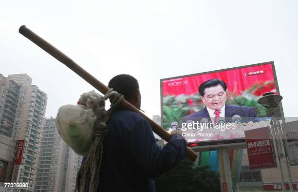 Worker watches a screen showing Chinese President Hu Jintao delivering a speech during opening ceremony the 17th National Congress of the Communist...